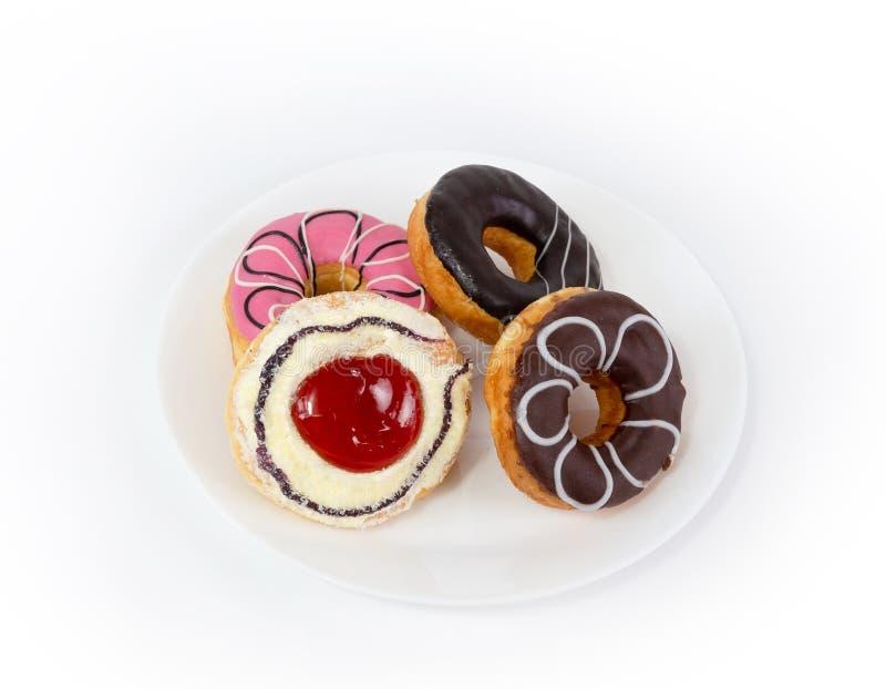 在板材的四个甜油炸圈饼在白色背景 库存照片