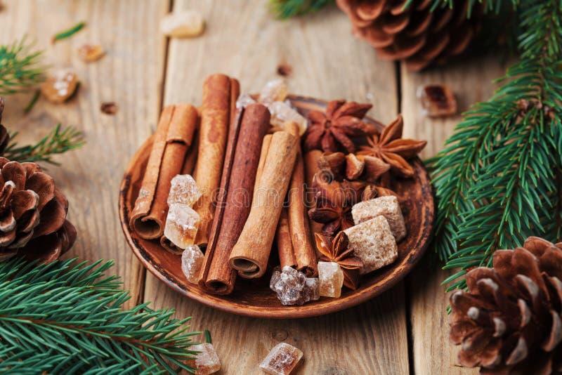 在板材的圣诞节香料在木土气桌上 茴香星、肉桂条和红糖 免版税库存照片