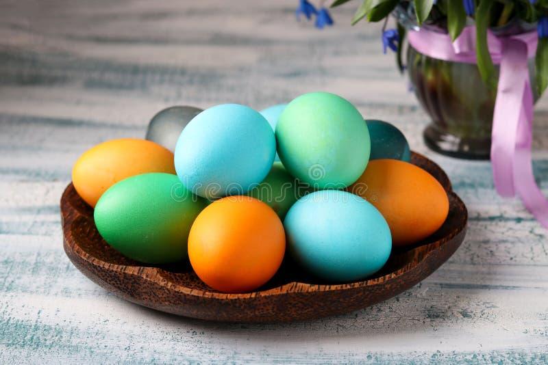 在板材的多彩多姿的在花瓶的复活节彩蛋和snowdrops 免版税库存照片