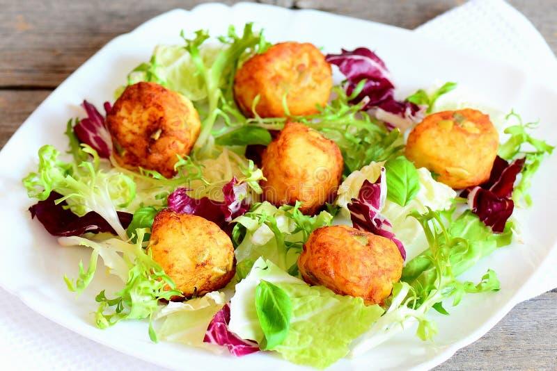 在板材的小金黄土豆球 与南瓜籽的酥脆土豆球 库存图片