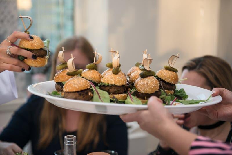 在板材的微型汉堡 采取从承办酒席服务侍者板材的妇女微型汉堡在事件 免版税图库摄影