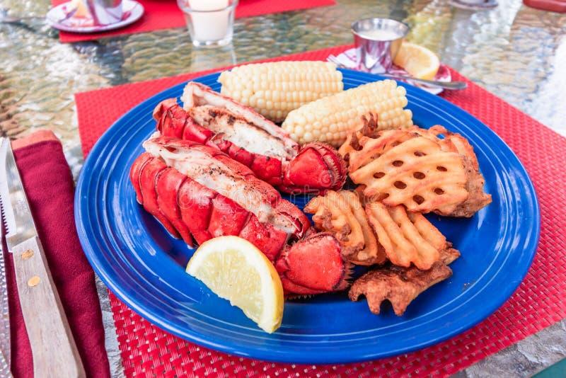 在板材的新鲜的缅因龙虾仁准备用黄油、玉米和土豆油炸物 免版税库存照片