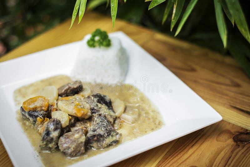在板材的有机牛肉和德国泡菜奶油色菜炖煮的食物 库存照片