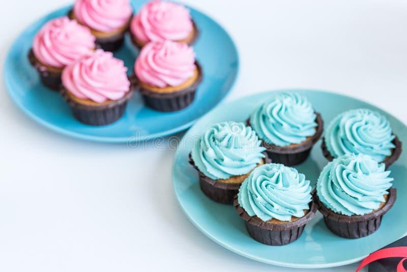 在板材的桃红色和蓝色杯形蛋糕在白色桌,婴儿送礼会党概念上 库存图片