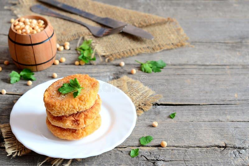 在板材的油煎的豌豆炸肉排 从黄色烹调的健康素食主义者炸肉排烘干了豌豆和装饰用荷兰芹 叉子,刀子 库存图片