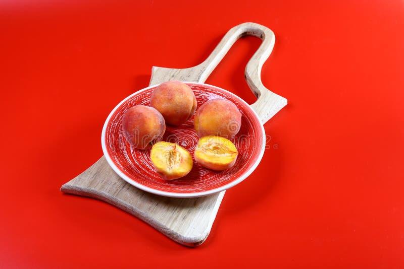 在板材的甜新鲜的桃子在红色背景在船上被隔绝 文本的空位 顶视图 免版税图库摄影