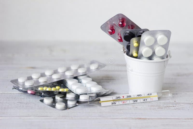 在板材的白色,红色,黑和黄色片剂在一个装饰桶,水银温度表 医学,健康概念 免版税库存图片