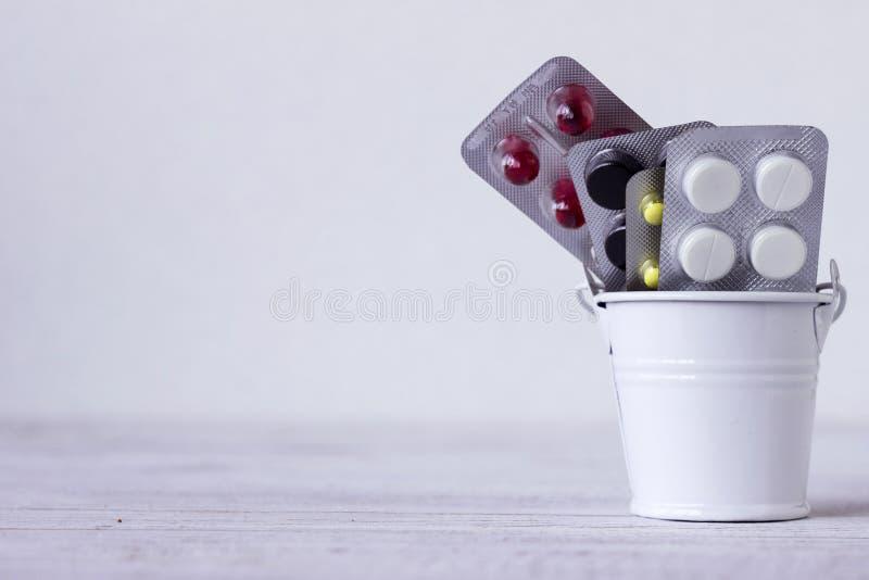 在板材的白色,红色,黑和黄色片剂在一个装饰桶,白色背景 医学,健康概念 图库摄影