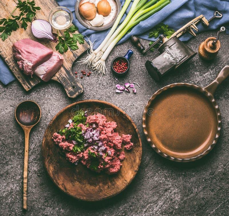 在板材的绞肉有烹调的有成份的匙子在土气厨房用桌背景 免版税图库摄影