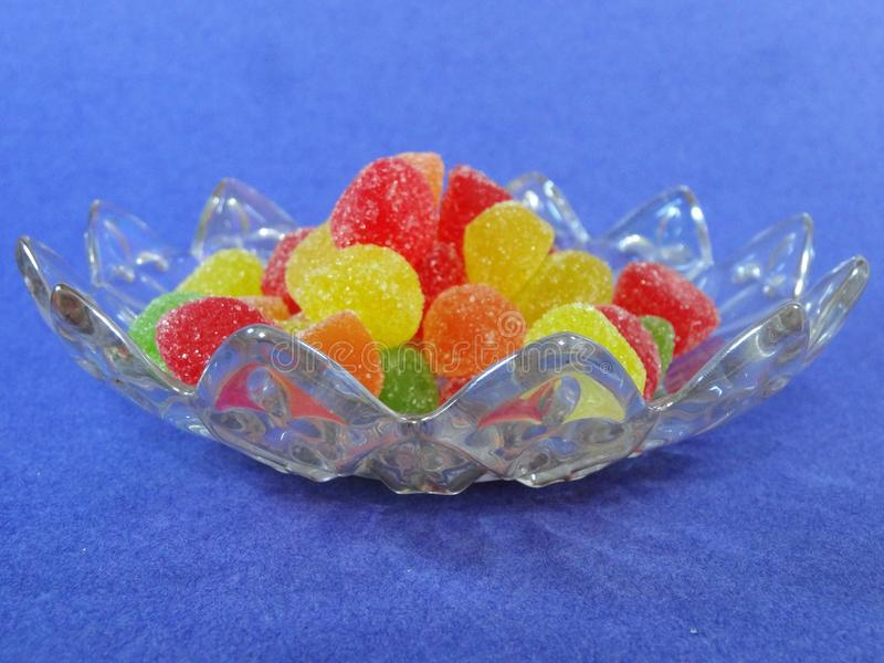 在板材的胶粘的糖果一个蓝色背景侧面视图 免版税库存图片