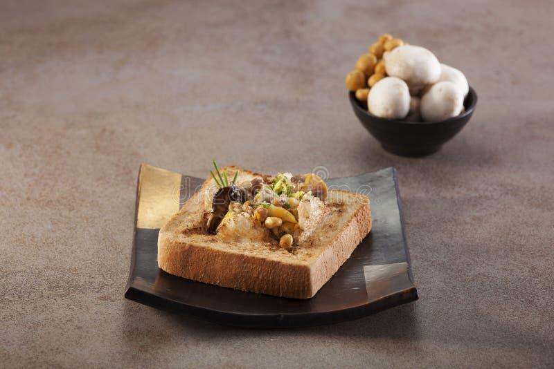在板材的被烘烤的蘑菇多士箱子在灰色背景中 库存图片