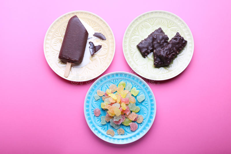 在板材,桃红色背景的不同的鲜美甜点 顶视图 免版税库存照片