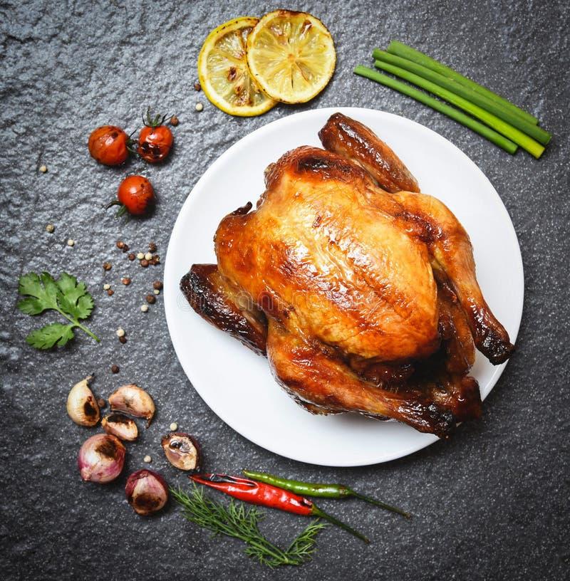 在板材-被烘烤的整鸡的烤鸡烤用在草本和香料和黑暗的背景 免版税库存图片