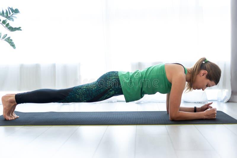 在板条姿势的年轻运动的妇女身分在健身席子 库存照片