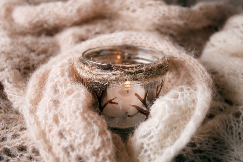 在板条木表上的升蜡烛白色被编织的毛线衣由窗口 舒适冬天秋天晚上 自然光地道平静 免版税库存图片