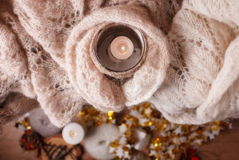 在板条木表上的升蜡烛白色被编织的毛线衣由窗口 舒适冬天秋天晚上 自然光地道平静 免版税图库摄影