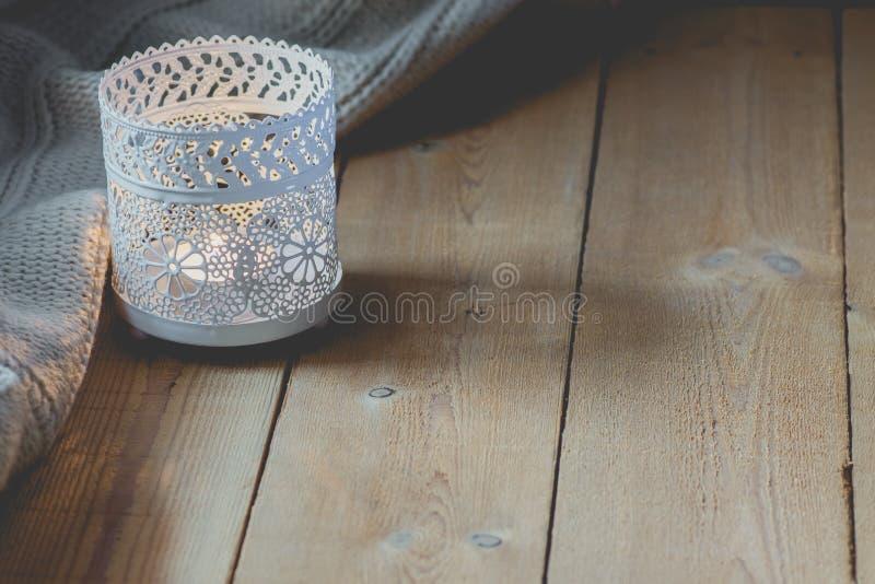 在板条木表上的升蜡烛白色被编织的毛线衣由窗口 舒适冬天秋天晚上 自然光平静的大气 免版税库存照片