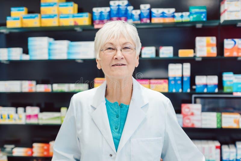 在架子前面的老练的资深药剂师在药房 免版税库存图片