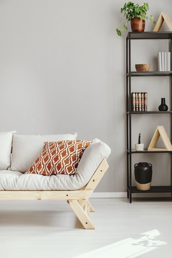 在架子旁边的斯堪的纳维亚沙发与辅助部件不同形式,与拷贝空间的真正的照片 免版税库存图片