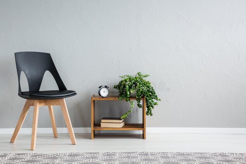 在架子旁边的时髦的黑椅子与两本书、时钟和绿色植物罐的 免版税图库摄影