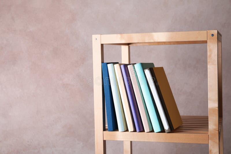 在架子的不同的书反对颜色背景 免版税库存照片