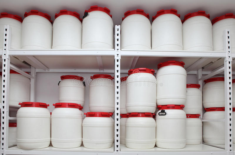 在架子的化工塑料桶在仓库 免版税库存照片