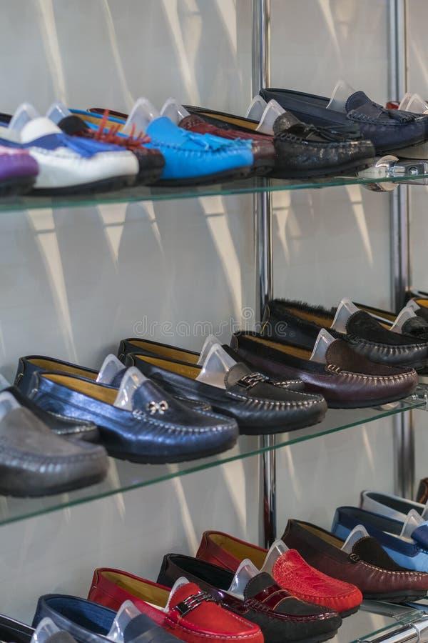 在架子的多彩多姿的皮革鹿皮鞋在商店 人的和妇女的皮鞋 多彩多姿的皮鞋 垂直 免版税库存图片