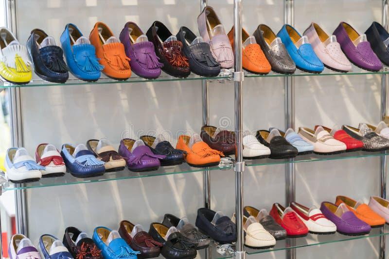 在架子的多彩多姿的皮革鹿皮鞋在商店 人的和妇女的皮鞋 多彩多姿的皮鞋 免版税图库摄影