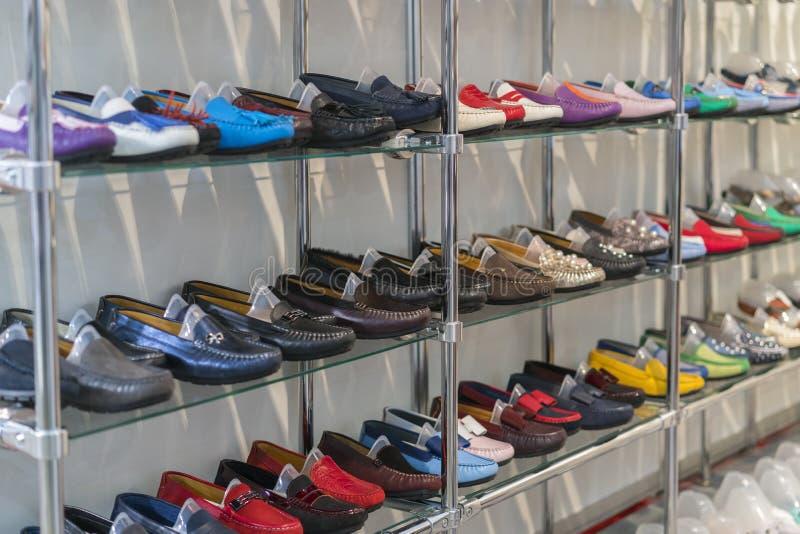 在架子的多彩多姿的皮革鹿皮鞋在商店 人的和妇女的皮鞋 多彩多姿的皮鞋 库存照片