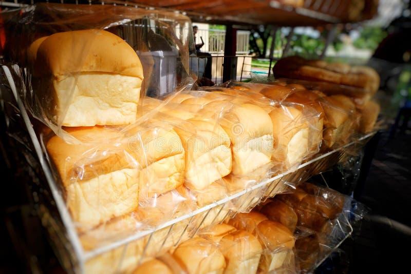 在架子的新鲜面包在户外商店或市场与阳光 图库摄影