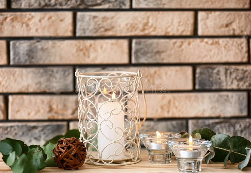 在架子的美好的灼烧的蜡烛在砖墙附近 库存照片