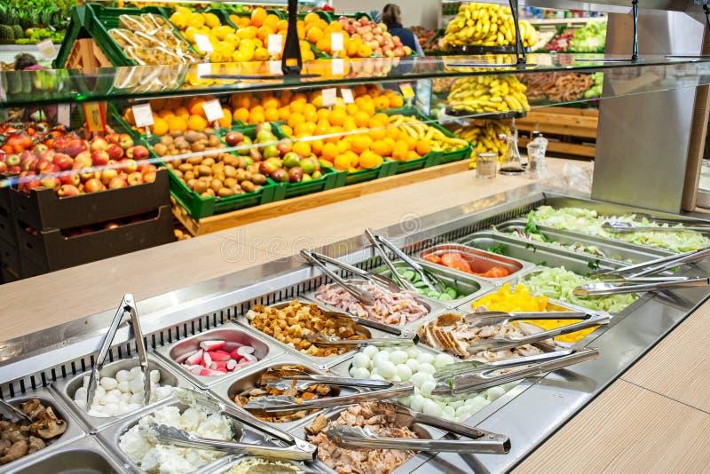 在架子背景的沙拉柜台与蔬菜和水果的在超级市场 库存图片
