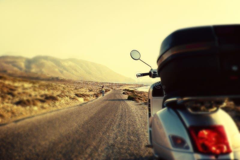 在柏油碎石地面乡下公路的滑行车 免版税库存图片