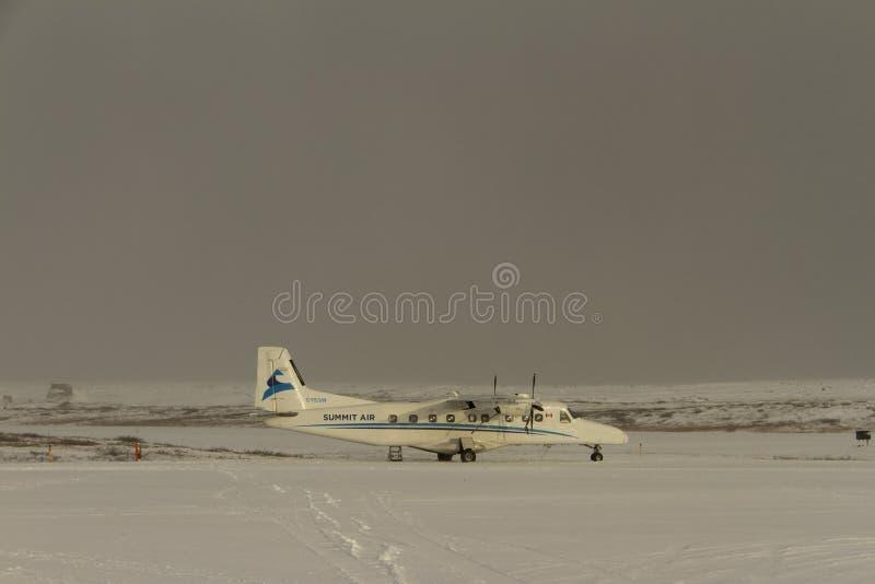 在柏油碎石地面找到的一架小飞机在与雪的早晨末期在地面上 库存图片