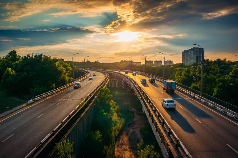 在柏油路或高速公路路线的城市交通在日落时间,全部汽车驾驶与最快速度,都市运输都市风景 库存照片