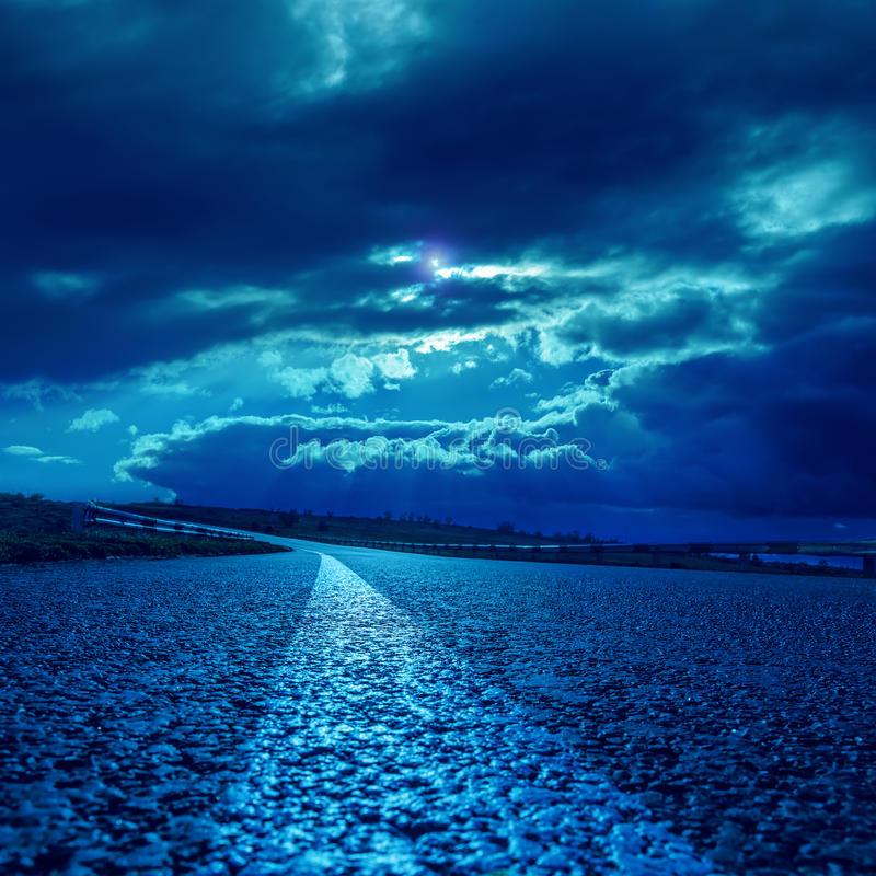 在柏油路的剧烈的云彩在黑暗的月光 免版税库存图片