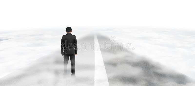 在柏油路的商人身分在云彩上的天空 免版税图库摄影