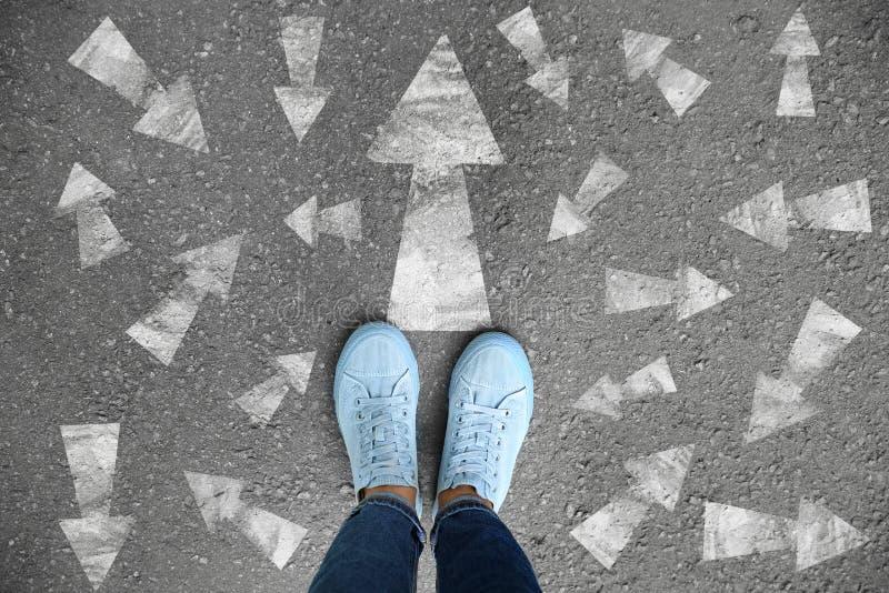 在柏油路的妇女身分有指向用不同的方向的箭头的 E 免版税库存照片