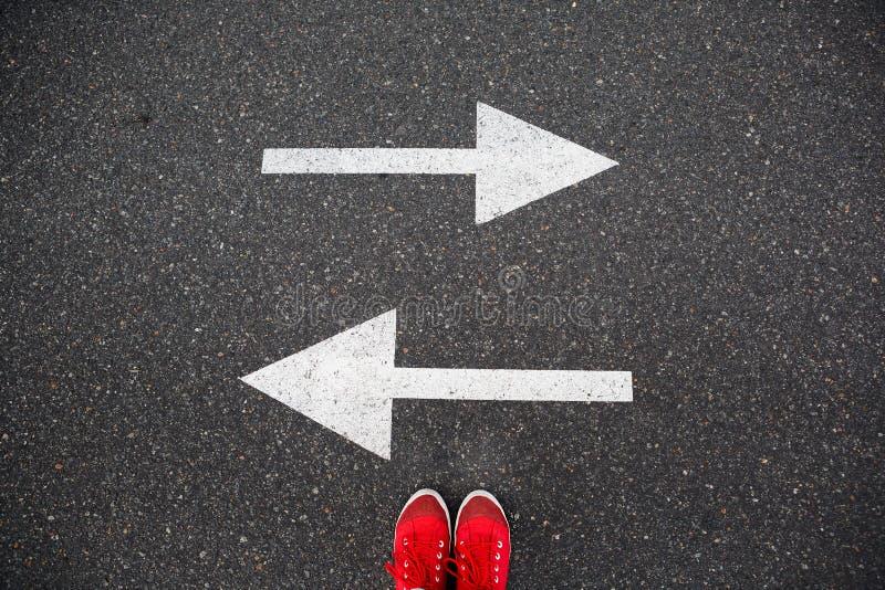 在柏油路的红色运动鞋有指向两个方向的拉长的箭头的 免版税库存照片