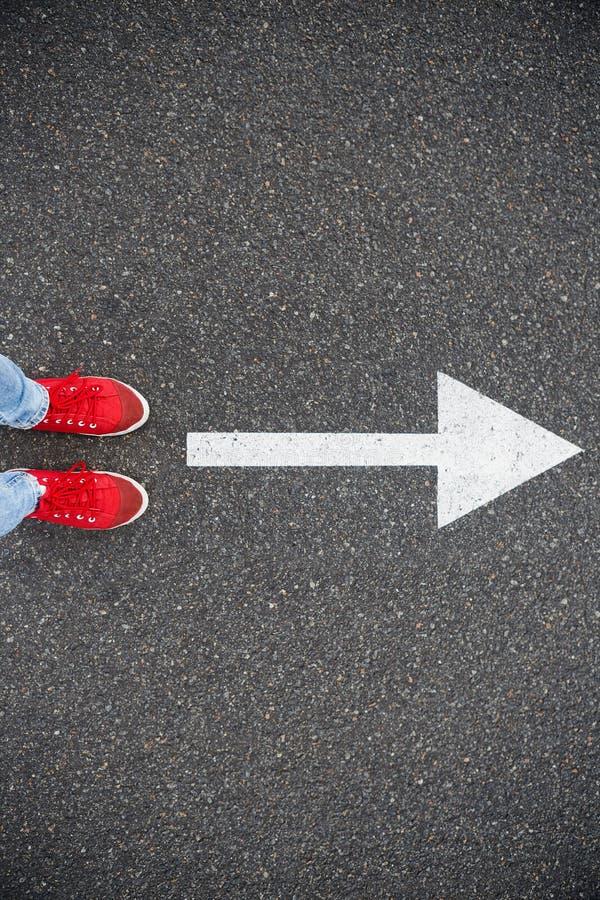 在柏油路的运动鞋有拉长的方向箭头的 免版税库存图片