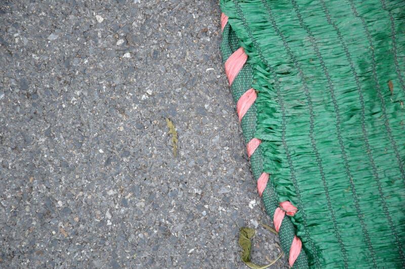 在柏油路的绿色太阳阴影网 免版税库存照片