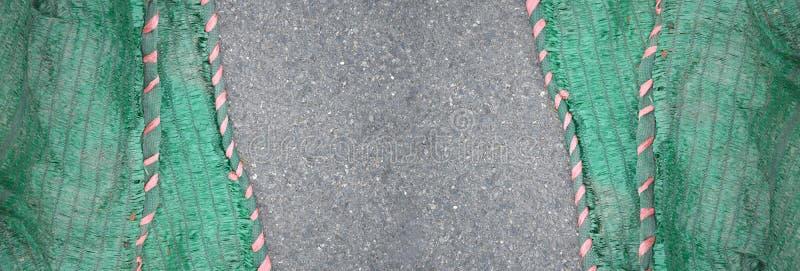 在柏油路纹理的绿色太阳阴影网 免版税图库摄影