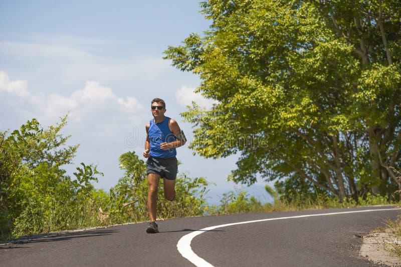 在柏油路连续锻炼的年轻有吸引力的体育赛跑者人训练每树和vegetati围拢的晴朗的夏天早晨 免版税库存照片