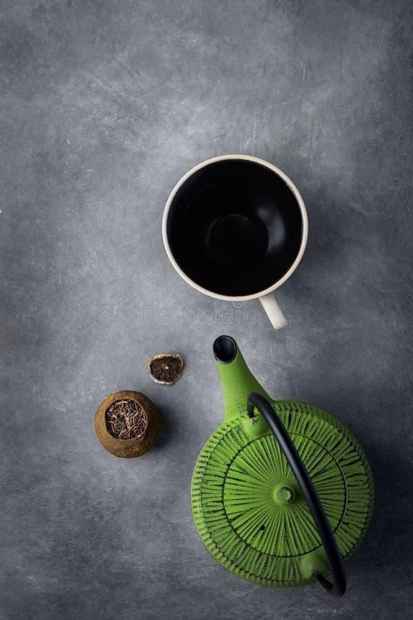 在柑橘果皮绿色水壶空的杯的年迈的被发酵的Pu erh茶在黑暗的石背景 中国日本亚洲烹调 库存图片