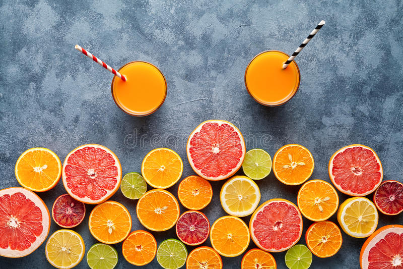 在柑橘水果背景平的位置的新汁液或圆滑的人维生素戒毒所饮料在具体桌上 库存图片