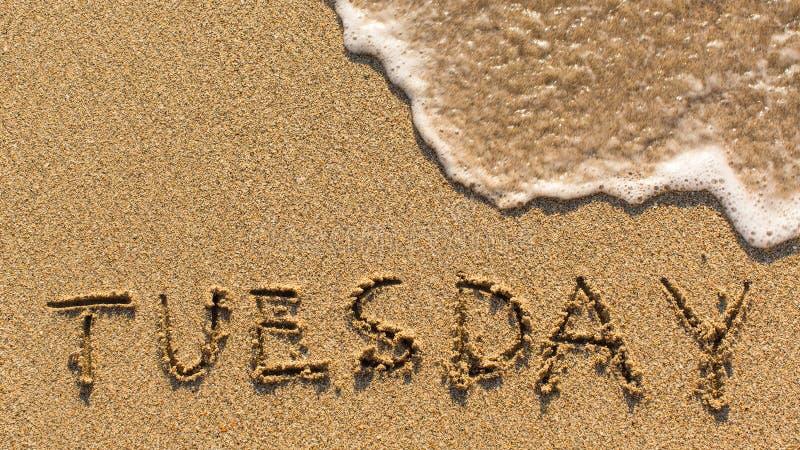 在柔和的海滩沙子的题字星期二与软的波浪 免版税库存图片