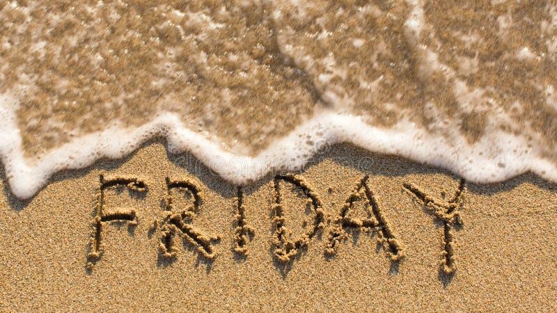 在柔和的海滩沙子的题字星期五与软的波浪 免版税图库摄影