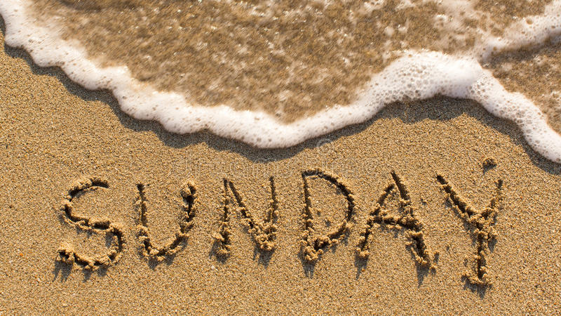 在柔和的海滩沙子的题字星期天与软的波浪 免版税库存照片