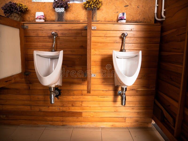 在柚木树木墙壁,巴恩室的白色尿壶 免版税库存图片