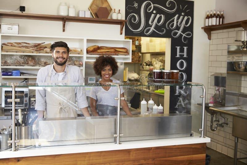 在柜台后的混合的族种夫妇在三明治酒吧 免版税库存照片